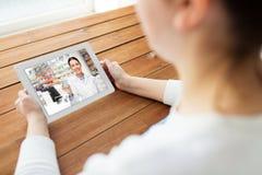 Mujer que tiene charla video con el farmacéutico en la tableta imagen de archivo libre de regalías