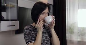 Mujer que tiene charla video usando el smartphone que disfruta de la charla al amigo almacen de metraje de vídeo