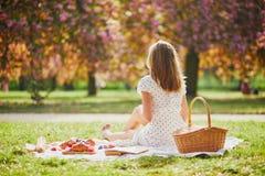 Mujer que tiene comida campestre en d?a de primavera soleado en parque durante la estaci?n de la flor de cerezo fotos de archivo libres de regalías