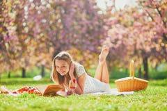 Mujer que tiene comida campestre en d?a de primavera soleado en parque durante la estaci?n de la flor de cerezo foto de archivo