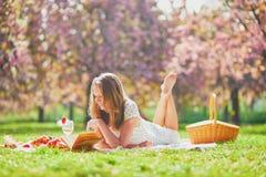 Mujer que tiene comida campestre en d?a de primavera soleado en parque durante la estaci?n de la flor de cerezo fotografía de archivo