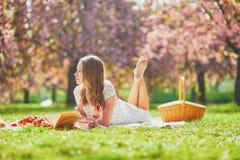 Mujer que tiene comida campestre en d?a de primavera soleado en parque durante la estaci?n de la flor de cerezo imagenes de archivo