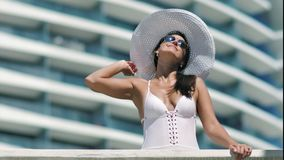 Mujer que tiene día de fiesta que toma el sol de goce al aire libre del buen tiempo en el balcón del hotel de lujo moderno almacen de video