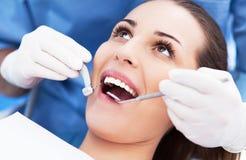 Mujer que tiene dientes examinados en los dentistas Imagenes de archivo
