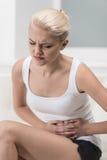 Mujer que tiene dolor abdominal en el sofá Fotos de archivo libres de regalías