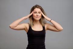 Mujer que tiene dolor de cabeza aislado en gris Fotografía de archivo