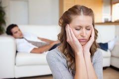 Mujer que tiene dolor de cabeza mientras que hombre que miente en el sofá detrás de ella Imagen de archivo