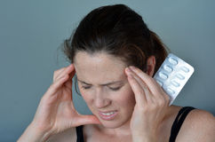 Mujer que tiene dolor de cabeza que toma píldoras Fotografía de archivo libre de regalías