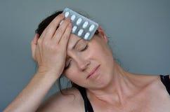 Mujer que tiene dolor de cabeza que toma píldoras Foto de archivo libre de regalías