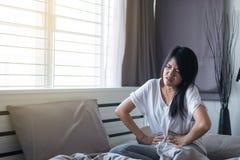 Mujer que tiene dolor de estómago doloroso, sufrimiento femenino del dolor abdominal Fotografía de archivo libre de regalías