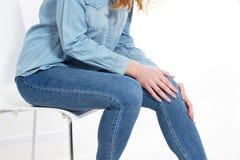 Mujer que tiene dolor de la rodilla en espacio m?dico de la copia de oficina foto de archivo libre de regalías