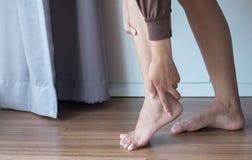 Mujer que tiene dolor del tobillo, sensación femenina agotada y dolorosa foto de archivo