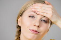 Mujer que tiene dolor principal Imagenes de archivo