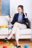 Mujer que tiene dos llamadas de teléfono al mismo tiempo Imagen de archivo libre de regalías