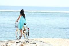 Mujer que tiene la diversión y bicicleta sonriente del montar a caballo en la playa Imagen de archivo libre de regalías