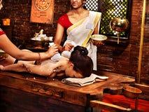 Mujer que tiene masaje con la bolsa del arroz. Fotografía de archivo