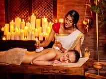 Mujer que tiene masaje con la bolsa del arroz Fotos de archivo
