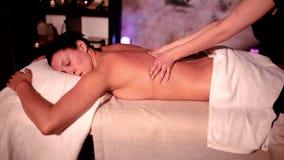 Mujer que tiene masaje de la carrocería en el salón del balneario Masajista que hace a la mujer del masaje del cuerpo en un salón almacen de metraje de vídeo