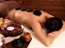 Mujer que tiene masaje de piedra en salón del balneario Imagen de archivo