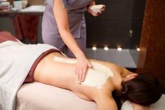 Mujer que tiene masaje trasero con crema en el balneario Foto de archivo libre de regalías