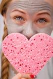 Mujer que tiene mascarilla gris que sostiene la esponja del corazón Imagenes de archivo