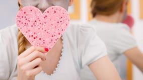 Mujer que tiene mascarilla gris que sostiene la esponja del corazón Foto de archivo