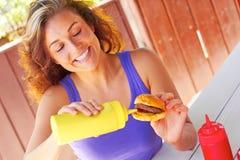 Mujer que tiene Mini Burger With Mustard Sauce Fotos de archivo libres de regalías