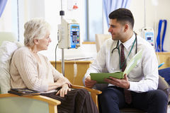 Mujer que tiene quimioterapia con el doctor Looking At Notes Imagen de archivo