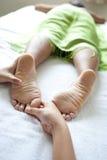 Mujer que tiene reflexology del pie del terapeuta Imagenes de archivo
