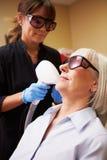 Mujer que tiene tratamiento del laser en la clínica de la belleza Imágenes de archivo libres de regalías