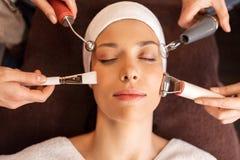 Mujer que tiene tratamiento facial del hydradermie en balneario imagenes de archivo