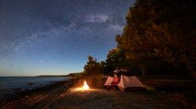 Mujer que tiene un resto en la noche que acampa cerca de la tienda tur?stica, hoguera en orilla de mar debajo del cielo estrellad foto de archivo libre de regalías
