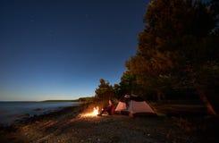Mujer que tiene un resto en la noche que acampa cerca de la tienda tur?stica, hoguera en orilla de mar debajo del cielo estrellad fotografía de archivo