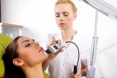 Mujer que tiene un tratamiento facial estimulante de un terapeuta imagen de archivo libre de regalías