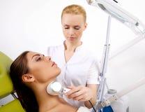 Mujer que tiene un tratamiento facial estimulante de un terapeuta fotos de archivo