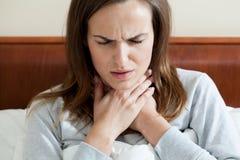 Mujer que tiene una garganta dolorida Foto de archivo libre de regalías
