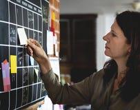 Mujer que tira de la nota pegajosa del plan del calendario en la pared fotos de archivo libres de regalías