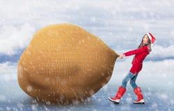 Mujer que tira del bolso de Papá Noel grande Imagen de archivo