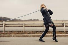 Mujer que tira del coche roto en el camino imagen de archivo