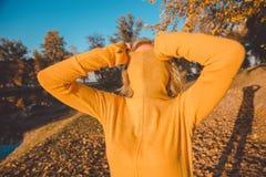 Mujer que tira del suéter anaranjado sobre su cara imagen de archivo libre de regalías