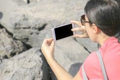 Mujer que tira una foto con el teléfono Fotografía de archivo libre de regalías