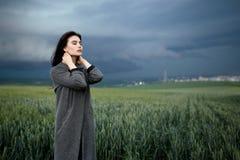 Mujer que toca el cuello con los ojos cerrados debajo del cielo nublado en el campo Visi?n horizontal imágenes de archivo libres de regalías