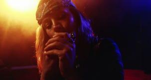 Mujer que toca la armónica en el club nocturno 4k almacen de video