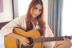 Mujer que toca la guitarra Foto de archivo libre de regalías