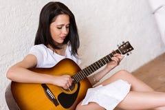 Mujer que toca la guitarra acústica Foto de archivo libre de regalías