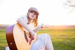 Mujer que toca la guitarra acústica en parque Fotos de archivo