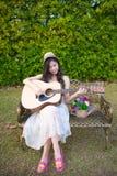 Mujer que toca la guitarra en jardín Fotografía de archivo