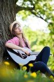 Mujer que toca la guitarra en parque Fotografía de archivo libre de regalías