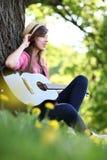 Mujer que toca la guitarra en parque Fotografía de archivo