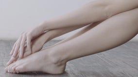 Mujer que toca suavemente sus piernas que se sientan en piso de madera con la pared blanca en fondo metrajes